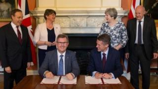DUP MP Sir Jeffrey Donaldson and Tory Chief Whip Gavin Williamson signed the deal in front of their party leaders