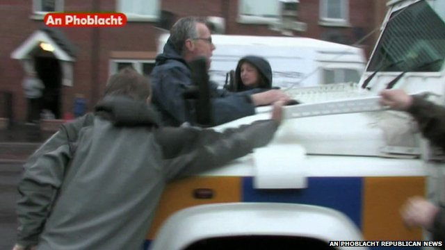 Gerry Kelly hangs on to front of police vehicle