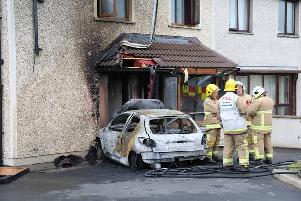 The scene on the Killyglen Road area of Larne where a car was been driven into a house and set on fire.