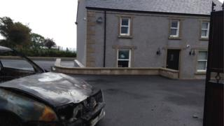 House with burnt-out car